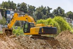 Yellow excavator machine with risen boom construction site. Excavator loader machine with risen boom construction site yellow excavator Stock Image