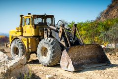 Big yellow old excavator working on a quarry for the extraction of sandstone royalty free stock photo