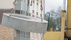 Yellow excavator rides concrete manhole ring on chains at building site. stock video