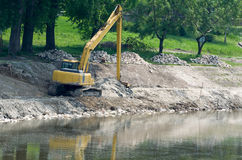 Yellow Excavator at Riverbank Stock Photography