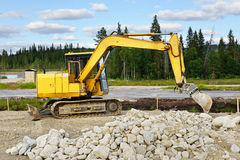 Yellow excavator in the road building Royalty Free Stock Photo