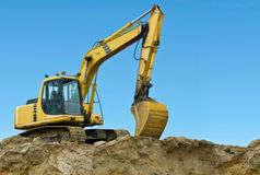 Yellow excavator on sand hill. Over blue sky Royalty Free Stock Images