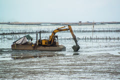Yellow Excavator in the sea Stock Images