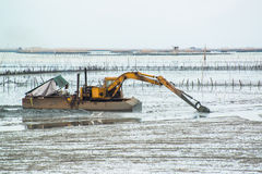 Yellow Excavator in the sea Stock Image