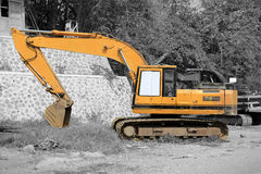 Yellow excavator, selective color. Big yellow excavator, conceptual image with isolated color over black and white background Stock Photo