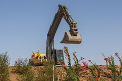 Yellow excavator stands on a hill Stock Photo