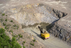 Yellow excavator stonecutter in a quarry for granite Stock Photos