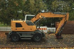 Yellow excavator in the street. Yellow excavator on the autumn city street Stock Image
