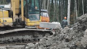 Yellow excavator swinging on chains concrete manhole ring at construction site. stock video