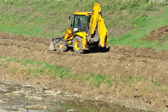Yellow excavator tractor on the riverbed Royalty Free Stock Photo