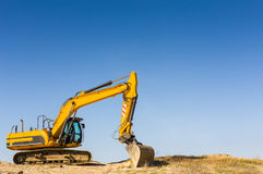 Yellow excavator under a clear blue sky. Heavy yellow excavator standing still on a sandy beach dune, under a clear blue sky Royalty Free Stock Photo