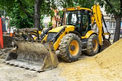 Free Yellow Excavator With A Bucket And Large Heap Of Sand At A Road Construction Site On A City Street On A Summer Day. Royalty Free Stock Photography - 149571747
