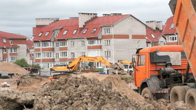 Yellow excavator working on construction site. MOSCOW, RUSSIA - JULY 07, 2017: Yellow excavator working on the background residential development. Construction stock video footage