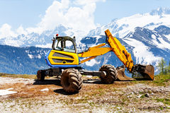 Yellow excavator working near mountains Royalty Free Stock Images
