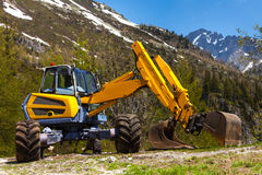 Yellow excavator working near mountains Stock Photos