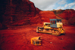 Yellow excavators at red rock quarry. Colorful industrial view royalty free stock photography