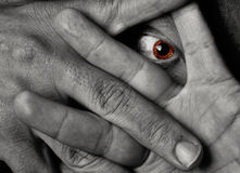 Yellow eye staring throug fingers Royalty Free Stock Photos