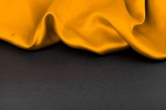 Yellow fabric on a black background Stock Images