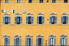 Yellow facade and blue windows Stock Images