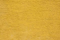 A yellow facade wall with structure. As a background stock photos