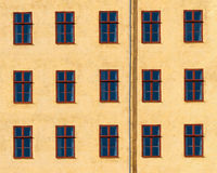 Yellow facade with windows. With red frames and a drainpipe Stock Images