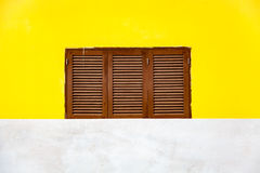 Yellow facade and a wooden window. A very bright yellow house front with brown wooden window with a closed wooden shutter Stock Image