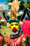 Yellow-faced man. Wabag, Papua New Guinea - August 2015: Native man with yellow and red colour and dots on his face wears large hat made of fur and feathers and Stock Photo