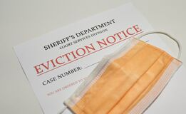 Yellow facial mask laying on top of the eviction note from sheriff`s department