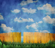 Wooden fence and sky. A yellow fence with a blue cloudy sky and behind a green grassy lawn Royalty Free Stock Image