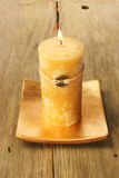 Yellow Feng Shui candle. On rustic wood royalty free stock photography