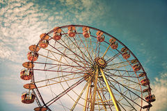 Yellow ferris wheel against a blue sky in vintage style Royalty Free Stock Photo