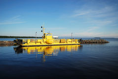 Yellow ferry in the blue water of Manamansalo Royalty Free Stock Image