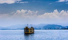 Yellow Ferry With Mountain And City At Background Royalty Free Stock Photography