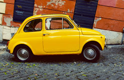 Yellow Fiat 500 parked in Rome. Royalty Free Stock Photo
