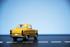 Yellow fifties toy model car. Classic fifties scale model toy car from back view royalty free stock photo