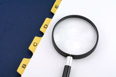 Yellow file divider and magnifier Stock Photography