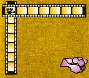 Yellow film strip and pink camera. Abstract yellow film strip frame with cloth background and pink camera Stock Photo