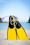 Yellow fins and snorkelling mask on beach in summer Royalty Free Stock Photography