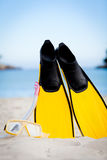 Yellow fins and snorkelling mask on beach in summer Royalty Free Stock Image