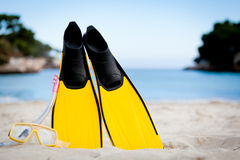 Yellow fins and snorkelling mask on beach in summer Stock Photos