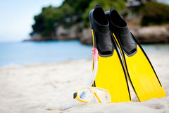 Yellow fins and snorkelling mask on beach in summer Stock Photo