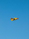 Yellow fire fighter airplane on blue sky Royalty Free Stock Photo