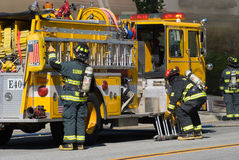 Yellow Fire Truck and Firefighters. Firefighters combating a house fire in a local neighborhood royalty free stock images