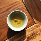 A yellow fish in the cup. Ceramic cups on the annatto furniture, the sunshine and the shadow in the water Stock Photo
