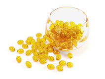 Yellow  fish oil capsules in glass bowl with clipping path. Illustration of yellow  fish oil capsules in glass bowl with clipping path Stock Image