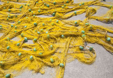 Yellow fishing net. Closeup of yellow fishing net with blue float laying on the ground Royalty Free Stock Image