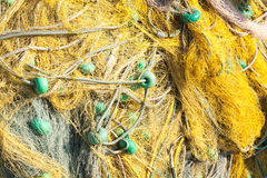 Yellow fishing net with green details drying on a pier Stock Image