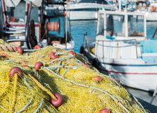 Yellow fishing nets stacked up near the water stock photo