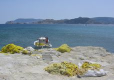 Yellow nets from fishing on a white rock with a fishing-boat, the sea and mountains in distance . Milos Island in Greece. Yellow fishing nets. White rock in Stock Photo
