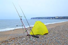Yellow fishing tent on a pebble beach. Near town of Seaton in Devon royalty free stock photo